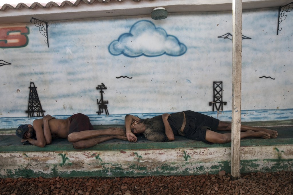 Fishermen nap in front of a mural of Lake Maracaibo, full of oil rigs, after working to catch crabs in the lake in Cabimas, near Maracaibo, Venezuela,...