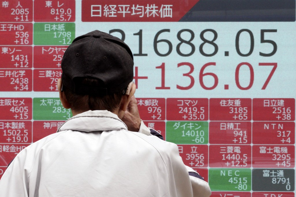 A man looks at an electronic stock board showing Japan's Nikkei 225 index at a securities firm in Tokyo Friday, Oct. 11, 2019. Asian stock markets fol