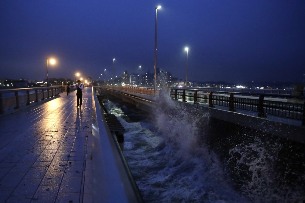 A man walks along the bridge connecting to Enoshima Island in Fujisawa, west of Tokyo, Friday, Oct. 11, 2019. A powerful typhoon was forecast to bring