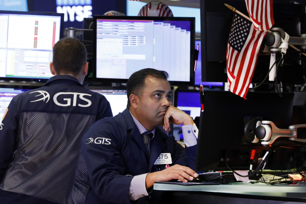 FILE - In this Oct. 2, 2019, file photo specialist Dilip Patel, right, works on the floor of the New York Stock Exchange. The U.S. stock market opens