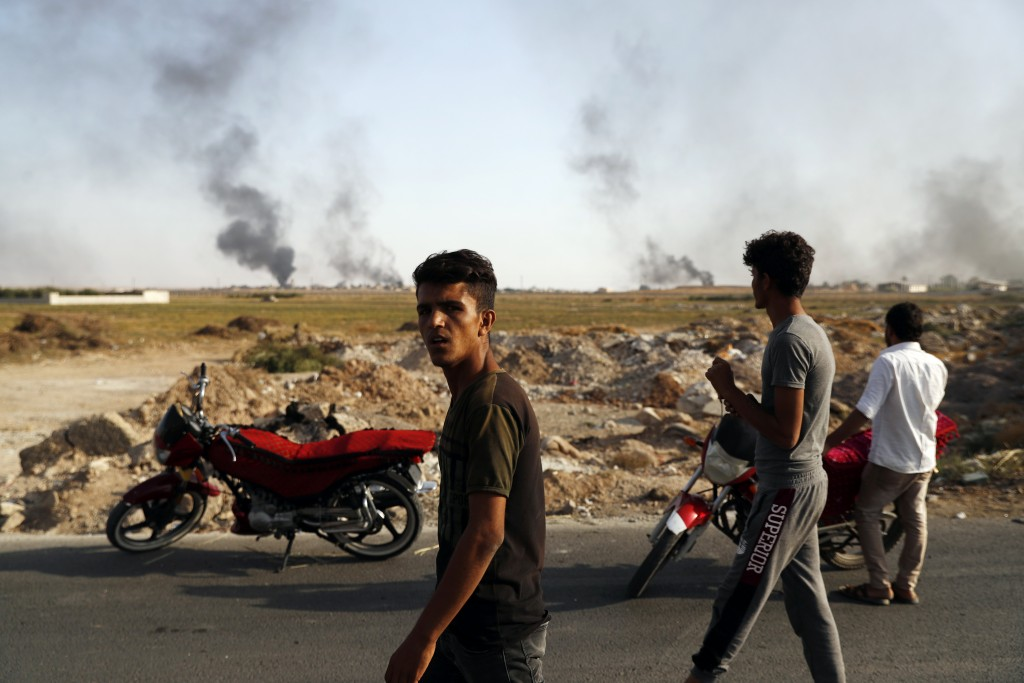 People in Akcakale, Sanliurfa province, southeastern Turkey, at the border with Syria, watch smoke billowing from targets inside Syria, during bombard...
