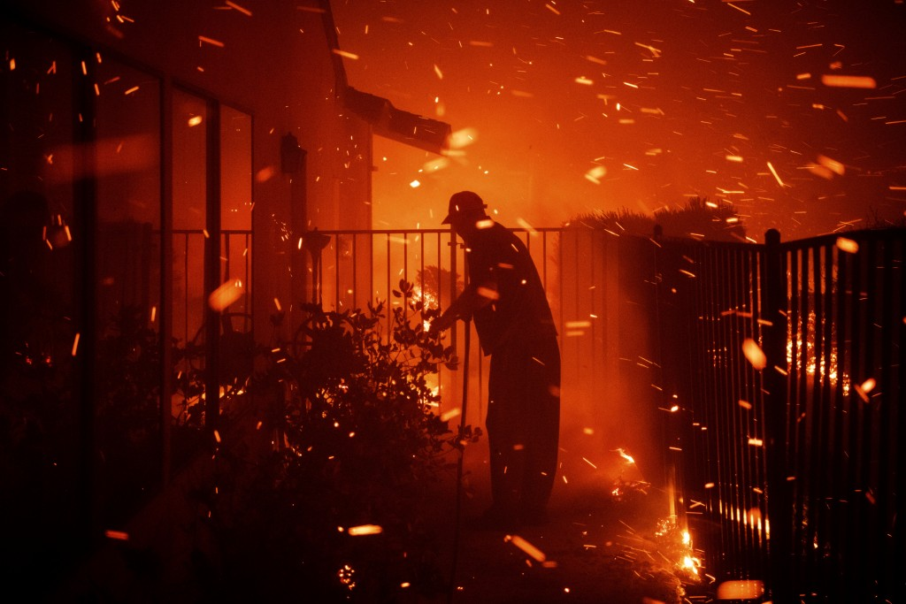 Jerry Rowe uses a garden hose to save his home on Beaufait Avenue from the Saddleridge fire in Granada Hills, Calif., Friday, Oct. 11, 2019. (AP Photo
