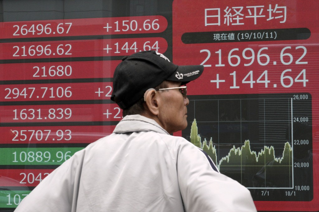 A man looks at an electronic stock board showing Japan's Nikkei 225 index at a securities firm in Tokyo Friday, Oct. 11, 2019. Asian stock markets fol...