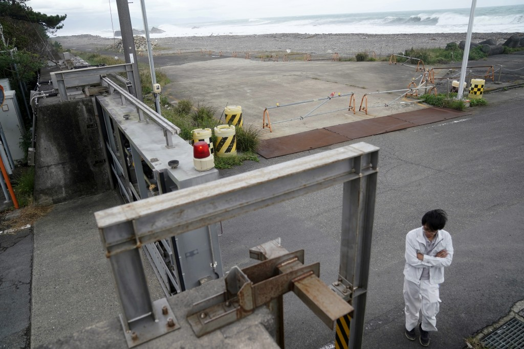A Kiho town official prepares to close a door of a coastal levee as Typhoon Hagibis approaches at a port in town of Kiho, Mie prefecture, central Japa