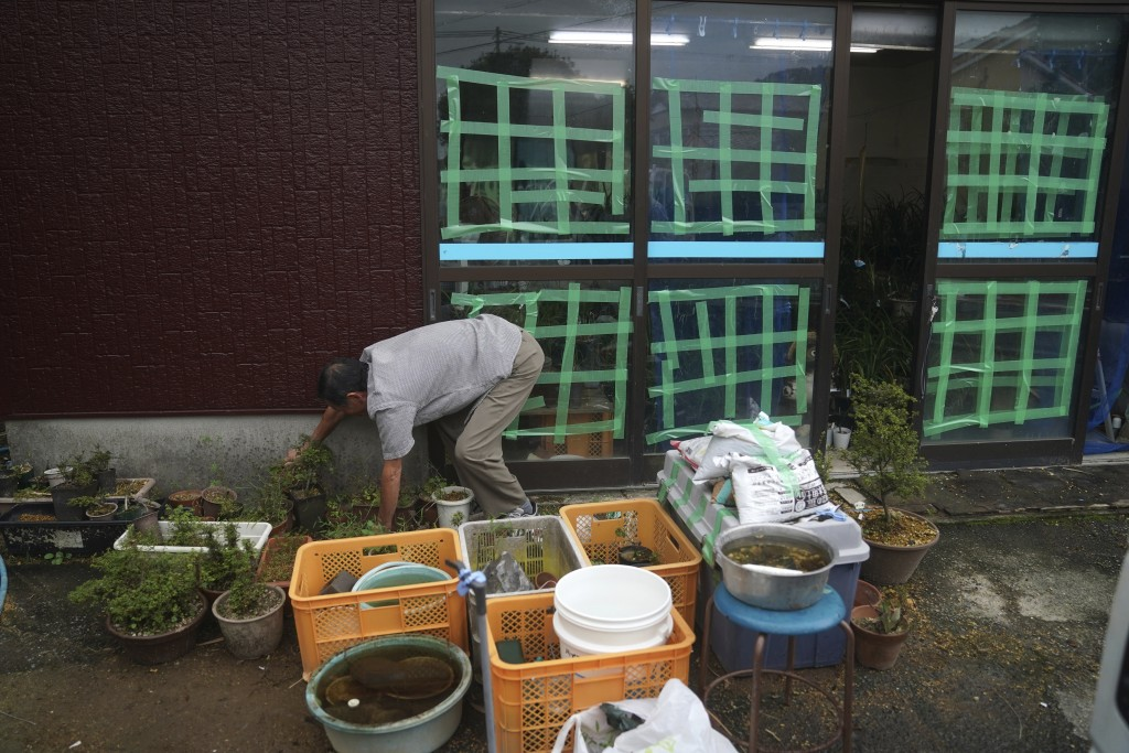 A man puts off things at a flower shop as Typhoon Hagibis approaches in town of Kiho, Mie Prefecture, Japan Friday, Oct. 11, 2019. A powerful typhoon ...