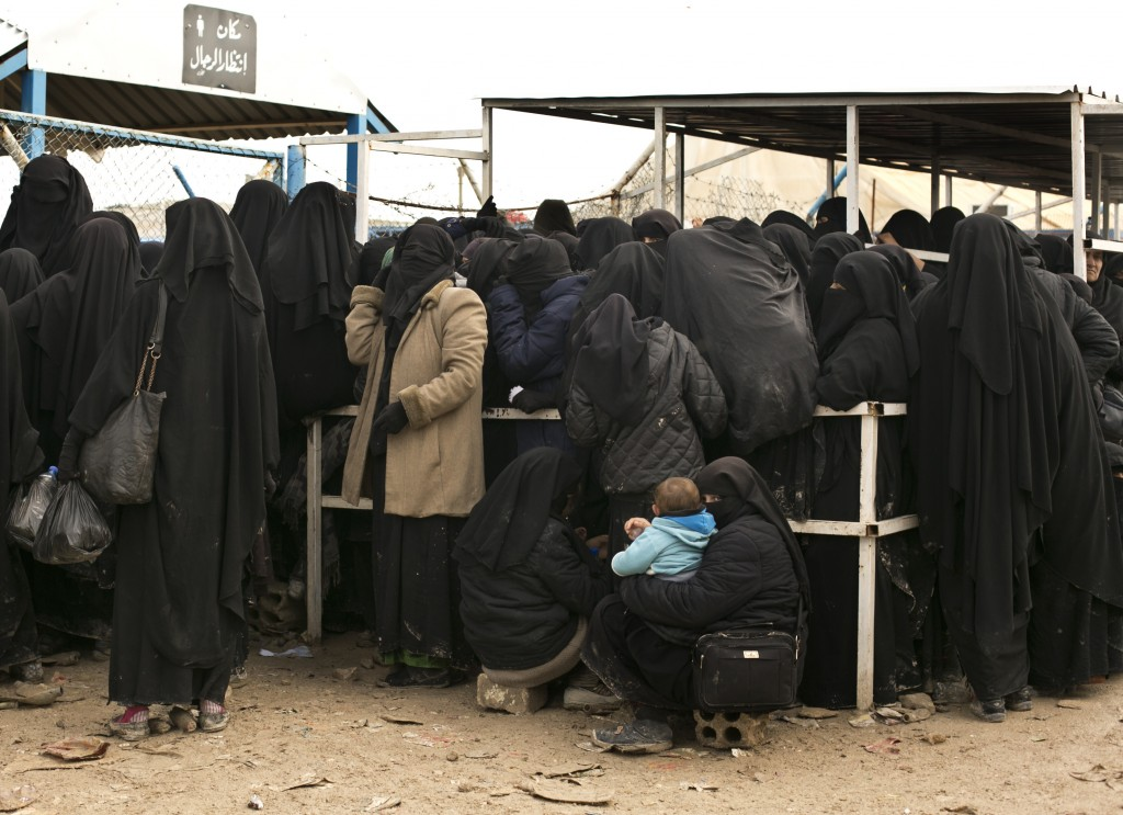 FILE - In this Sunday, March 31, 2019, photo, women line up for aid supplies at al-Hol camp in Hasakeh province, Syria.  As Turkish troops invade nort