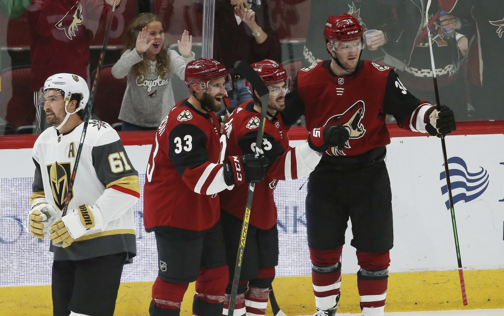 Arizona Coyotes right wing Conor Garland, second from right, celebrates his goal with Coyotes defenseman Alex Goligoski (33) and Coyotes right wing Ch...