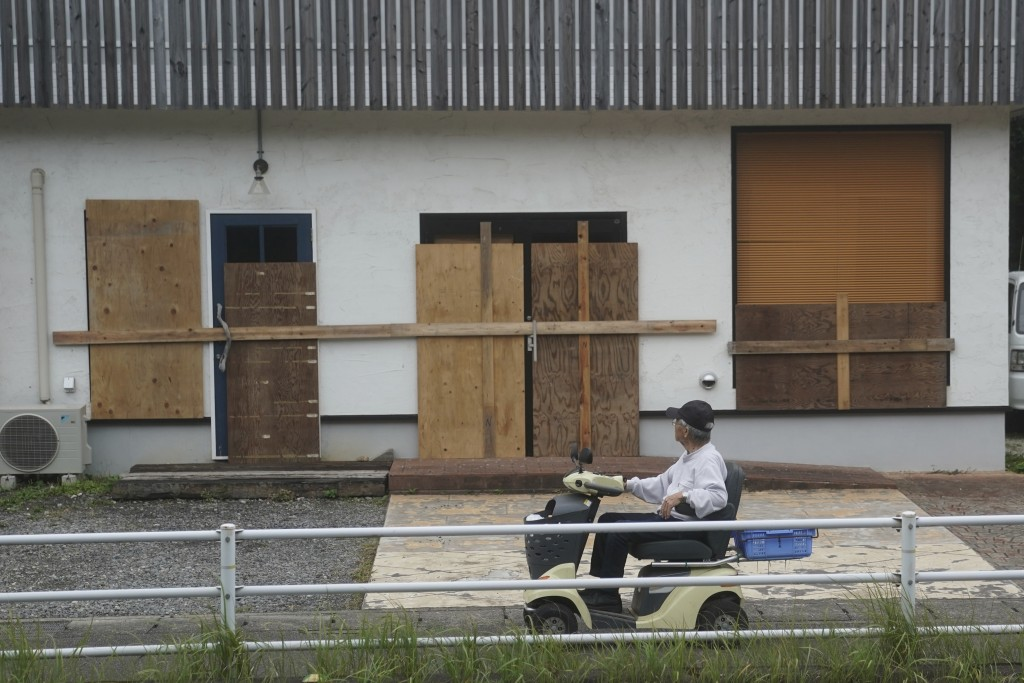 A man looks at a shop, protected by wood boards, as Typhoon Hagibis approaches in town of Kiho, Mie Prefecture, Japan Friday, Oct. 11, 2019. A powerfu...