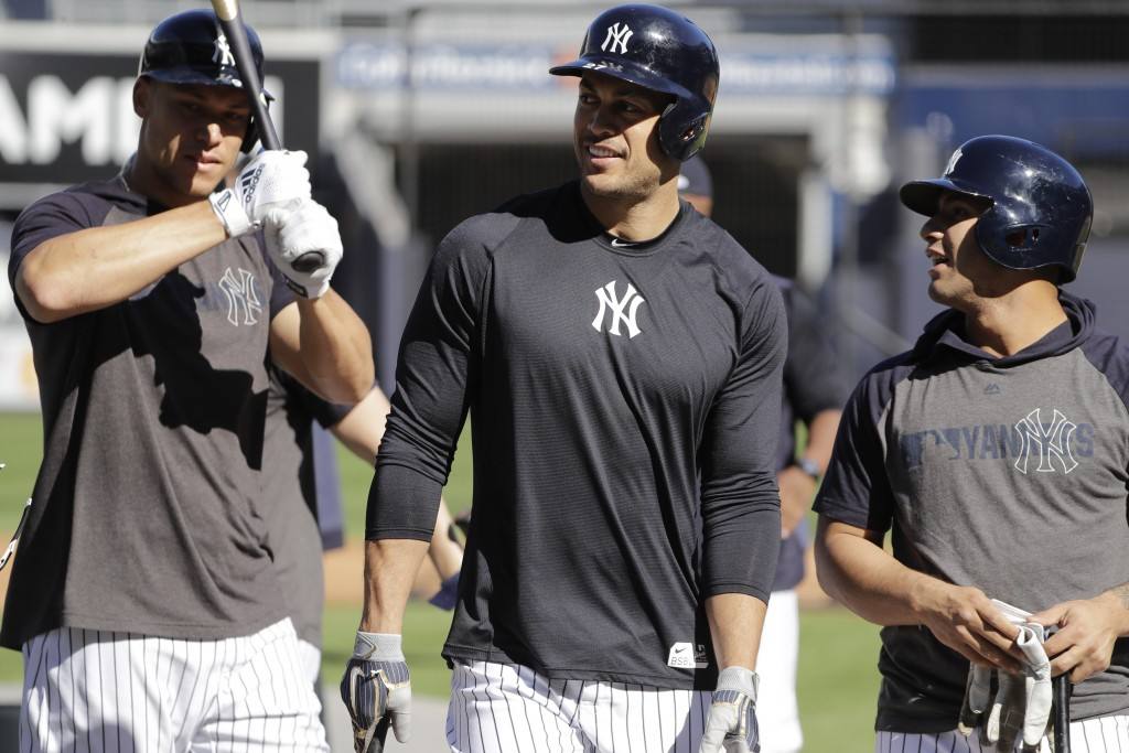 New York Yankees' Giancarlo Stanton, center, and Aaron Judge, left, walks with teammates during a practice at Yankee Stadium Thursday, Oct. 10, 2019,