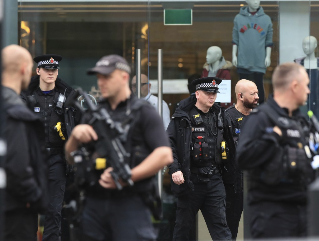Armed police officers outside the Arndale Centre in Manchester, England, Friday Oct. 11, 2019, after a stabbing incident at the shopping center that l