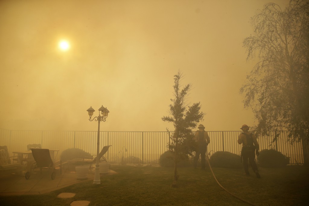 Firefighters make a stand on an advancing wildfire as smoke fills the air Friday, Oct. 11, 2019, in Porter Ranch, Calif. (AP Photo/Marcio Jose Sanchez...