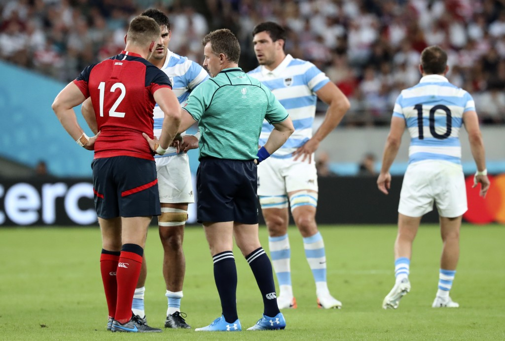 Referee Nigel Owens talks to team captain's England's Owen Farrell, left, and Argentina's Pablo Matera following a player scuffle during the Rugby Wor...
