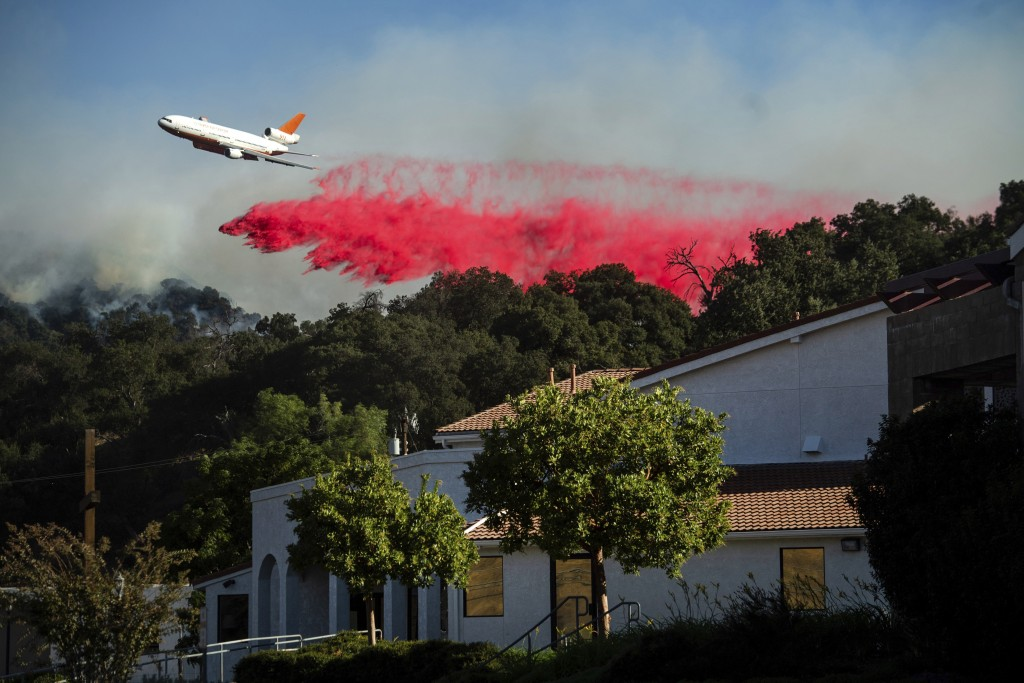 An air tanker drops retardant behind the Newhall Church of the Nazarene while battling the Saddleridge Fire in Newhall, Calif., on Friday, Oct. 11, 20...