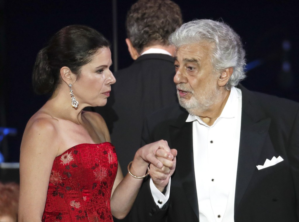 FILE - In this file photo taken on Aug. 28, 2019, Opera star Placido Domingo holds the hand of Ana Maria Martinez at the end of a concert in Szeged, H...