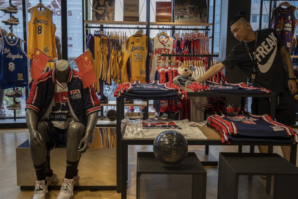 In this Friday, Oct. 11, 2019, photo, a sales person adjust a mascot doll at a NBA merchandise store in Beijing. When Houston Rockets' general manager