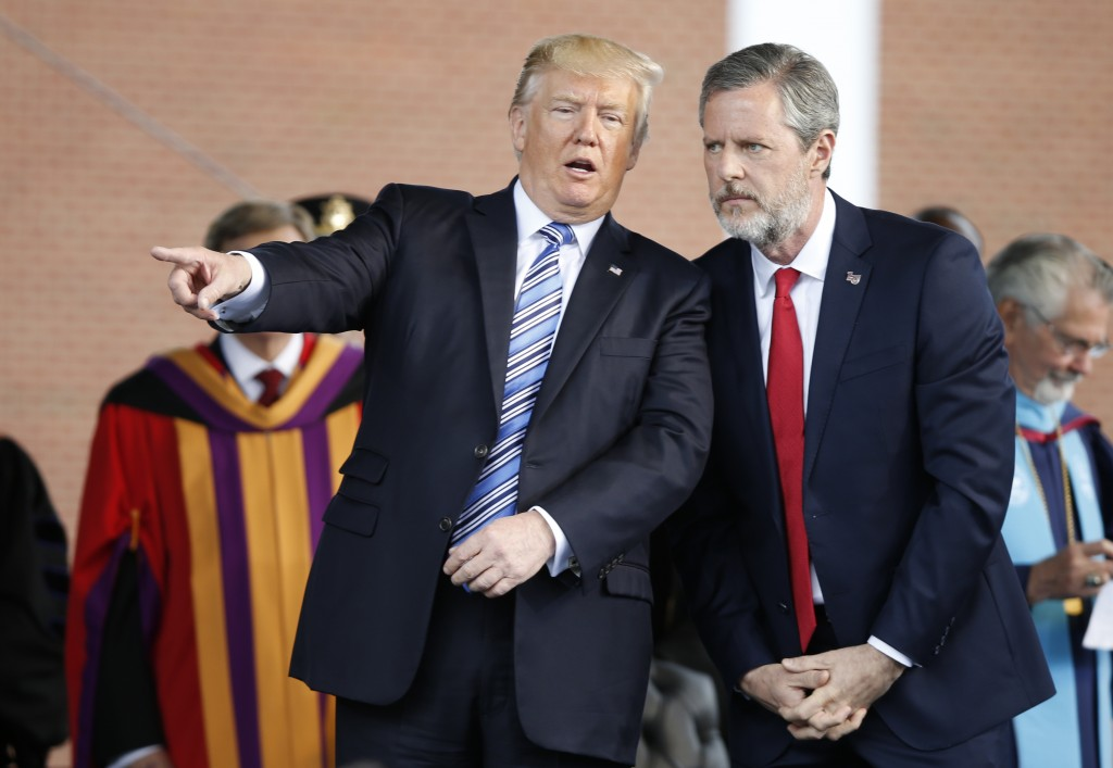 FILE - In this May 13, 2017 file photo, President Donald Trump gestures as he stands with Liberty University president, Jerry Falwell Jr., right, duri
