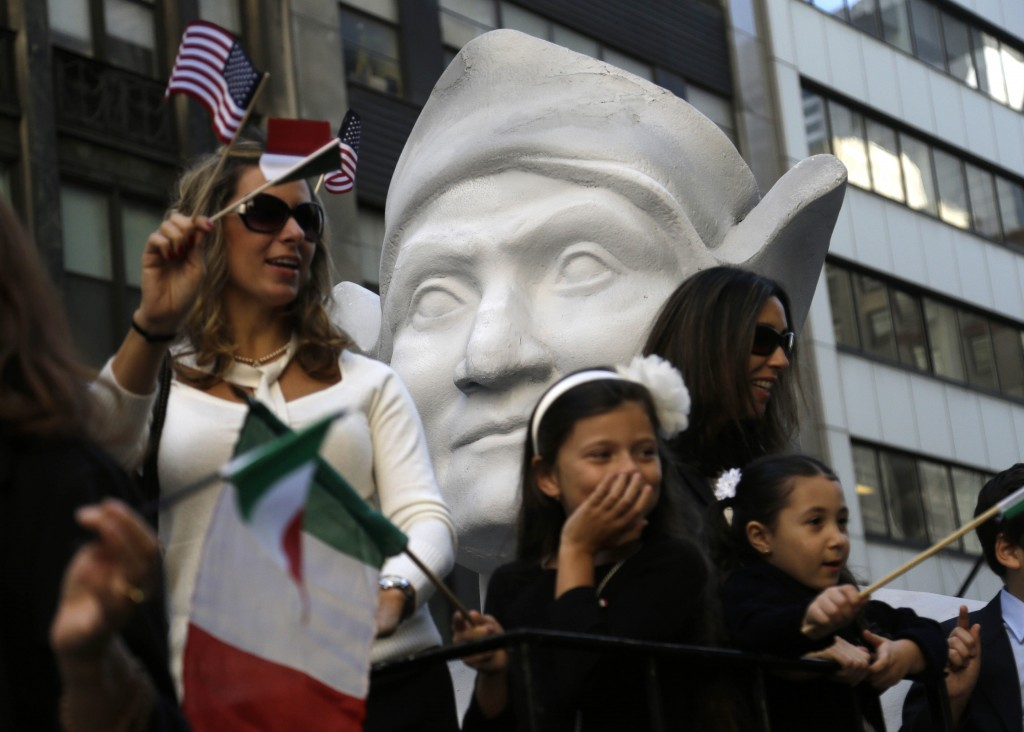 FILE - In this Oct. 12, 2015, file photo, participants in New York's Columbus Day Parade ride a float with a large bust of Columbus. The image and sto