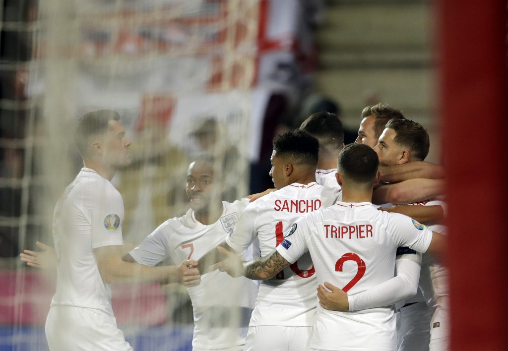 England's Harry Kane celebrates with teammates after scoring his side's opening goal from the penalty spot during the Euro 2020 group A qualifying soc...