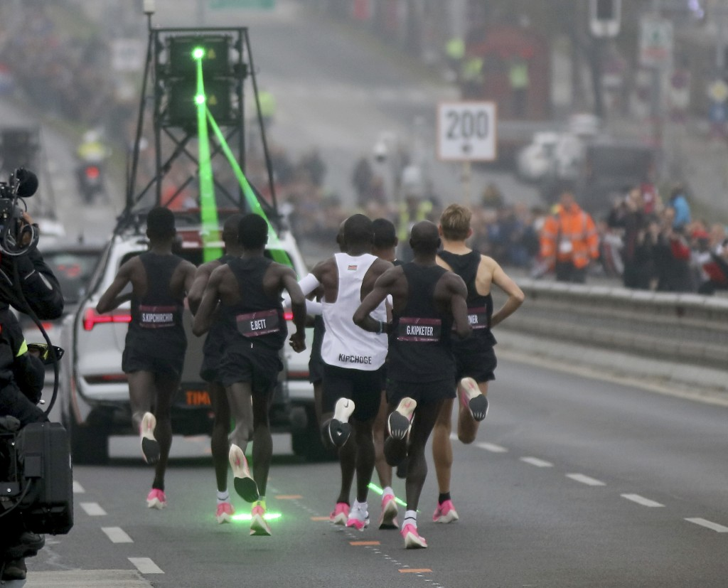 Marathon runner Eliud Kipchoge from Kenya, white vest, and his first pacemaking team run on the Reichsbrucke during the INEOS 1:59 Challenge attempt t...