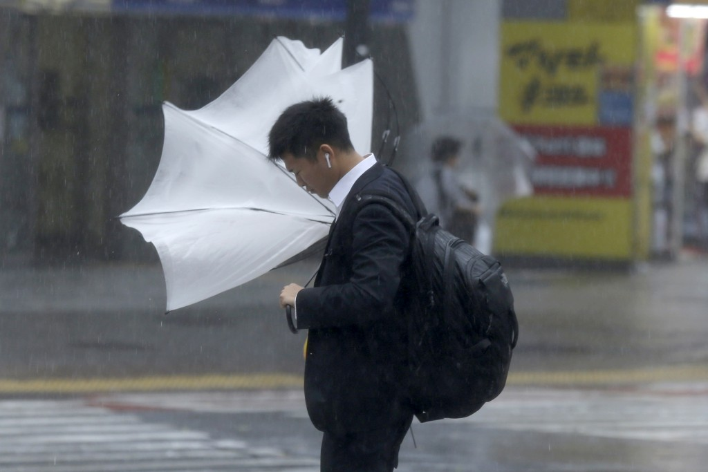A man struggles with his umbrella against strong wind at a crossing in Shibuya district, Tokyo Saturday, Oct. 12, 2019. Tokyo and surrounding areas br