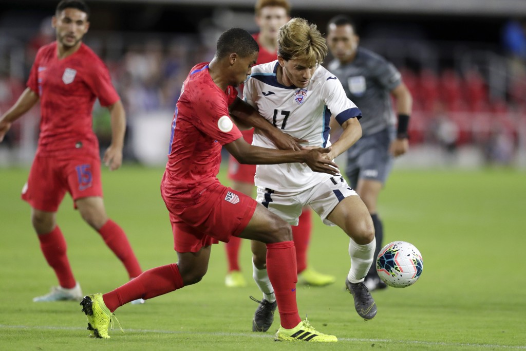 Cuba's Jean Carlos Rodriguez, right, and United States' Reggie Cannon compete for the ball during the first half of a CONCACAF Nations League soccer m