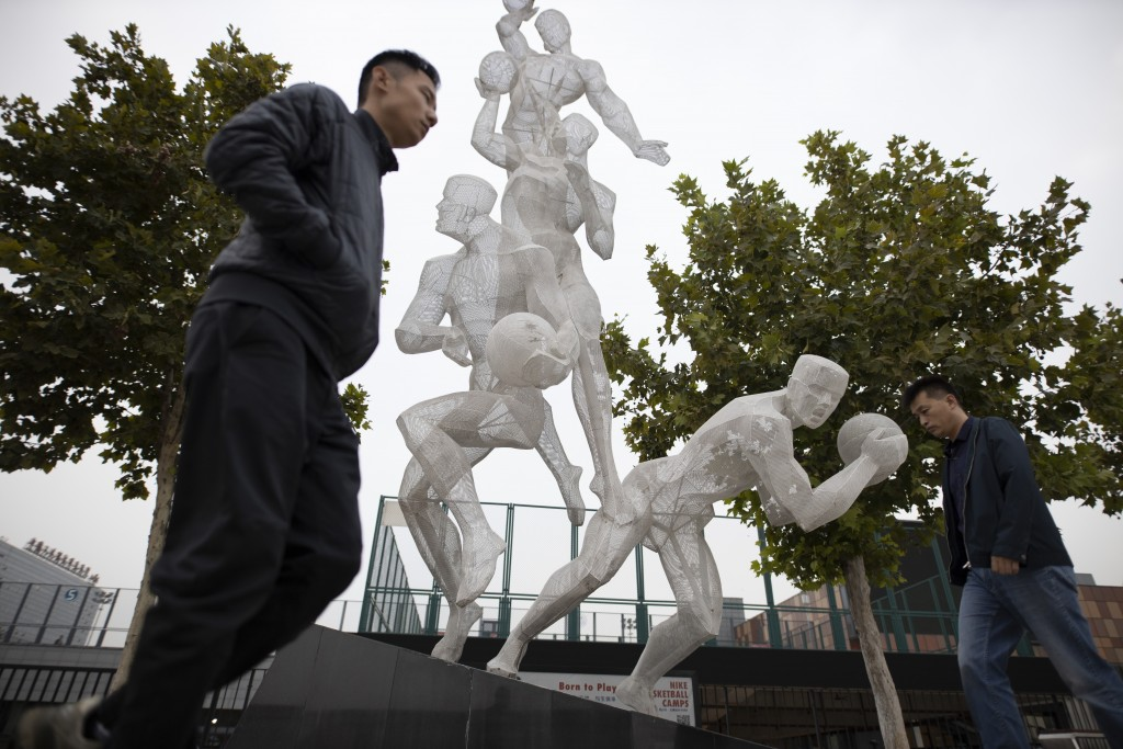 In this Friday, Oct. 11, 2019, photo, Chinese men walk by a sculpture depicting basketball players in Beijing. When Houston Rocket's general manager D