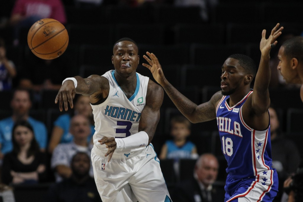 Charlotte Hornets guard Terry Rozier III, left, passes around Philadelphia 76ers guard Shake Milton in the first half of a preseason NBA basketball ga