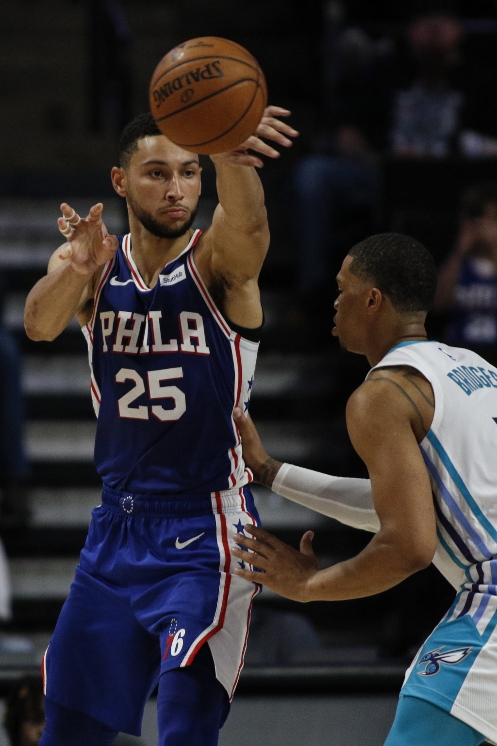 Philadelphia 76ers guard Ben Simmons, left, passes around Charlotte Hornets forward Miles Bridges in the second half of a preseason NBA basketball gam...