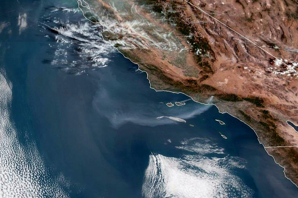 This satellite image from the National Oceanic and Atmospheric Administration (NOAA) shows a plume of smoke from the Saddleridge wildfire streaming ou