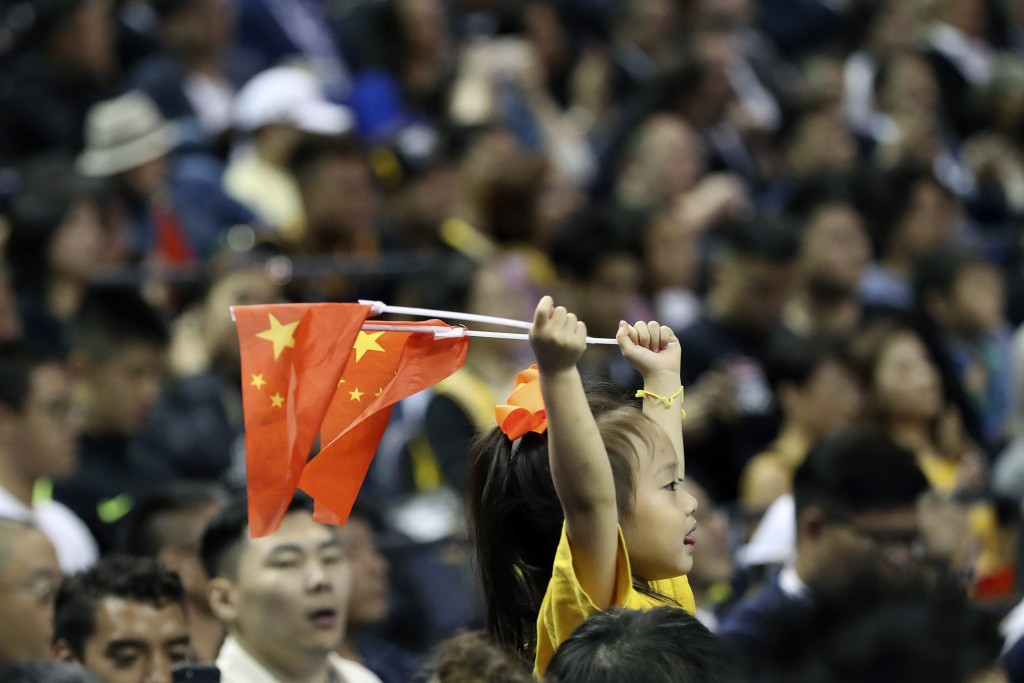 FILE - In this Oct. 10, 2019 file photo, a child holds up two Chinese national flags as she watches a preseason NBA basketball game between the Brookl