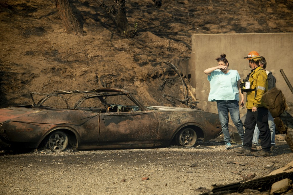 A resident surveys the scorched remains of her home and vehicle after the Saddleridge Fire burned through Granada Hills, Calif., on Friday, Oct. 11, 2...