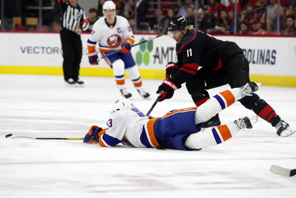 New York Islanders' Mathew Barzal (13) falls to the ice as he battles Carolina Hurricanes' Jordan Staal (11) during the second period of an NHL hockey...