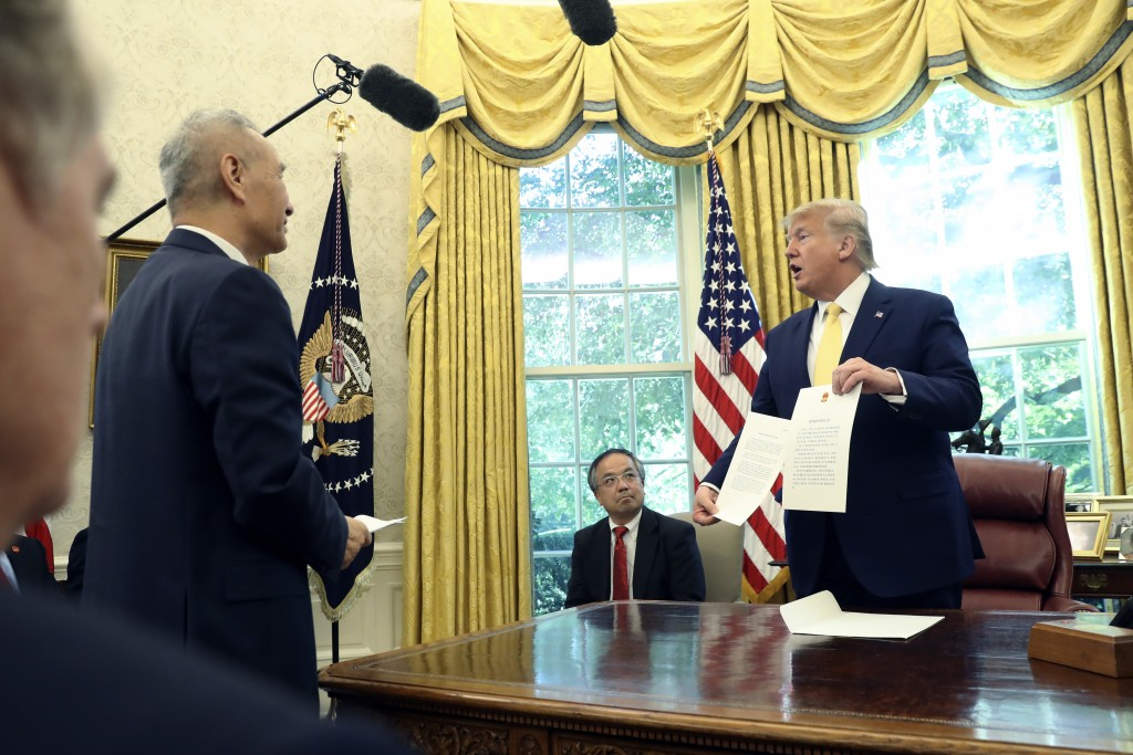 President Donald Trump holds a letter presented to him by Chinese Vice Premier Liu He in the Oval Office of the White House in Washington, Friday, Oct...