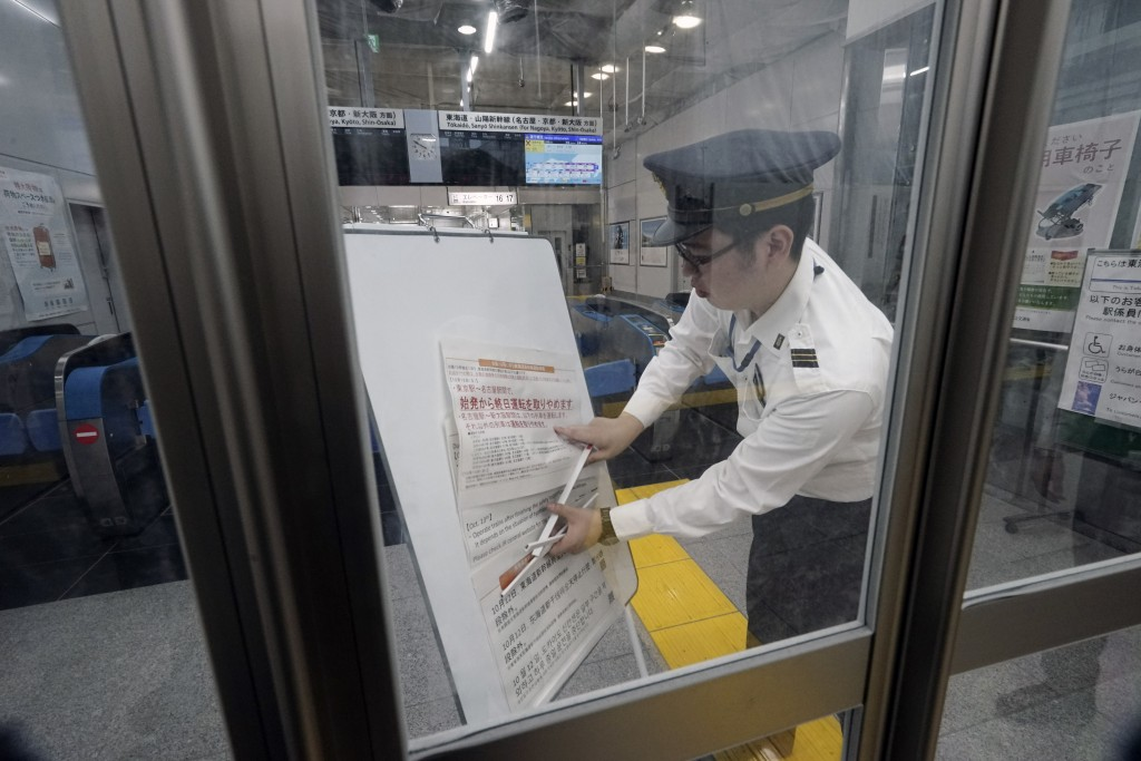 A staff member adjusts update notice paper on suspending operations of the Shinkansen or bullet train on Oct. 12-13 due to Typhoon Hagibis, at Tokyo S...
