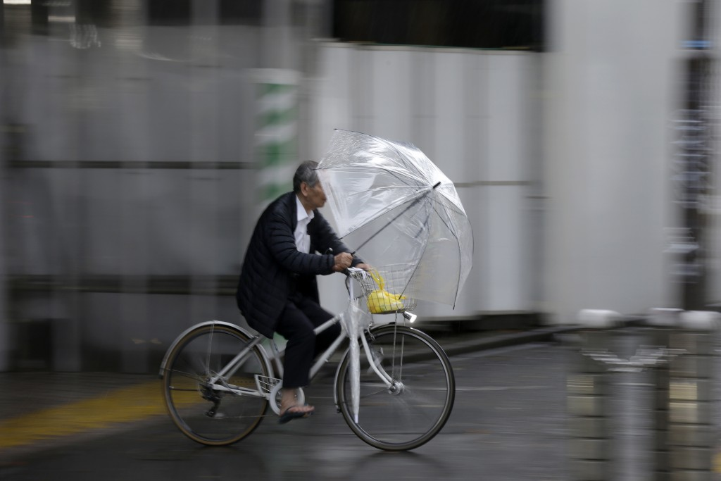 A man holds an umbrella while ride his bicycle in rain in Shibuya district, Tokyo Saturday, Oct. 12, 2019. Tokyo as surrounding areas braced for a pow