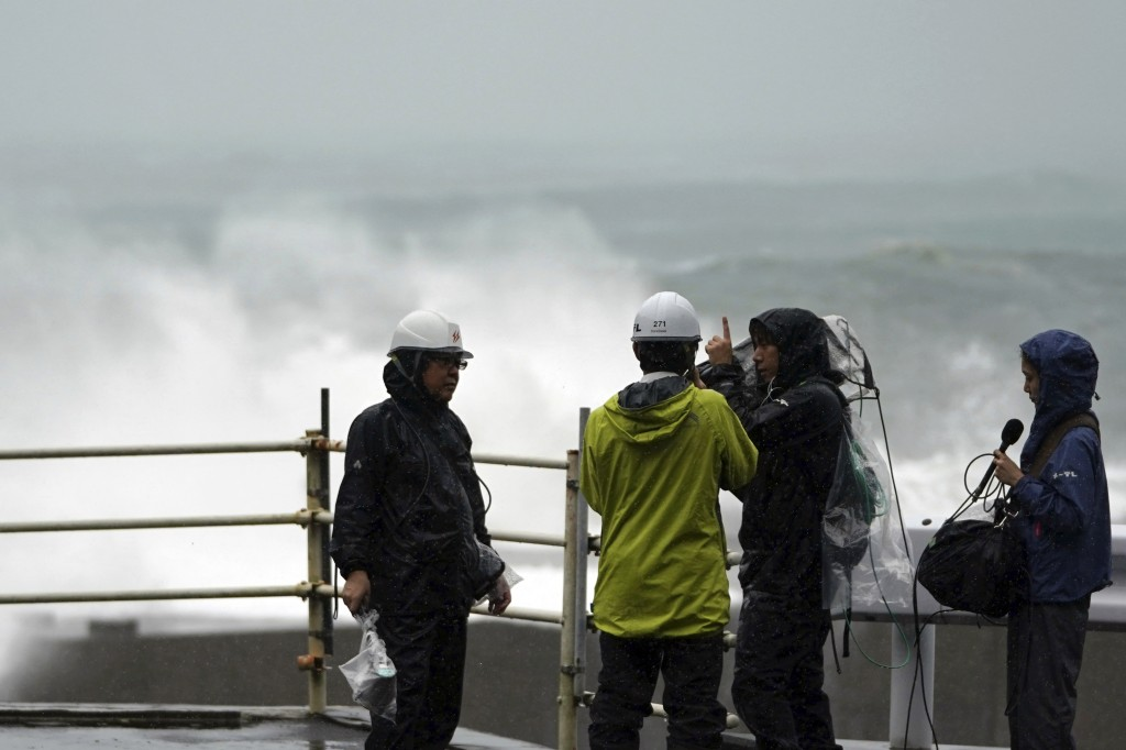 A local television crew reports on the surging waves as Typhoon Hagibis approaches a port in Kumano, Mie Prefecture, Japan, Saturday, Oct. 12, 2019. (...