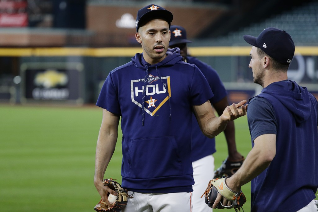 Houston Astros shortstop Carlos Correa, left, talks with teammate Alex Bregman, right, during a workout for a baseball American League Championship Se...