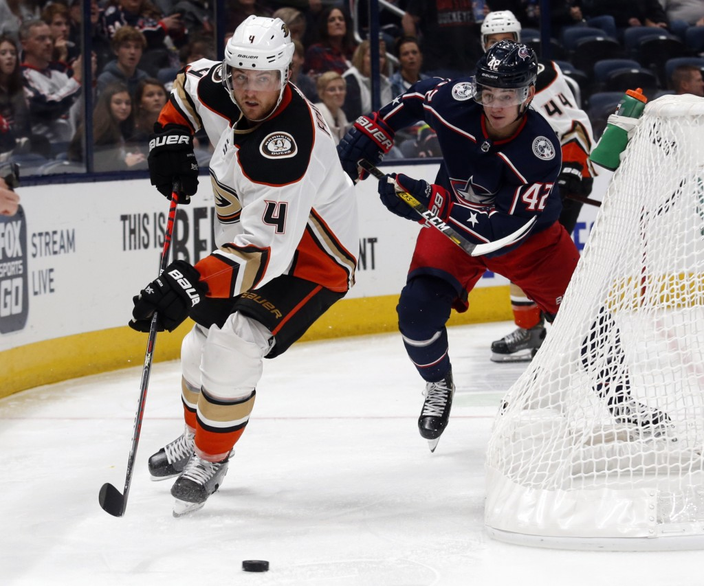 Anaheim Ducks defenseman Cam Fowler, left, controls the puck in front of Columbus Blue Jackets forward Alexandre Texier, of France, during the second