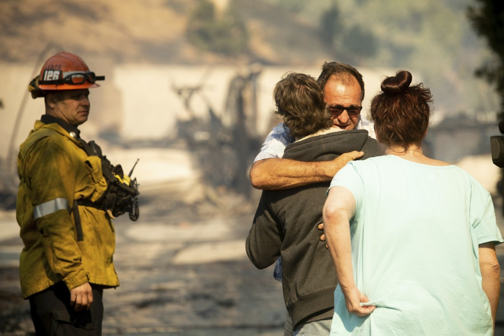 Eyed Jarjour comforts a neighbor who lost his Jolette Ave. home to the Saddleridge Fire on Friday, Oct. 11, 2019, in Granada Hills, Calif. (AP Photo/N...