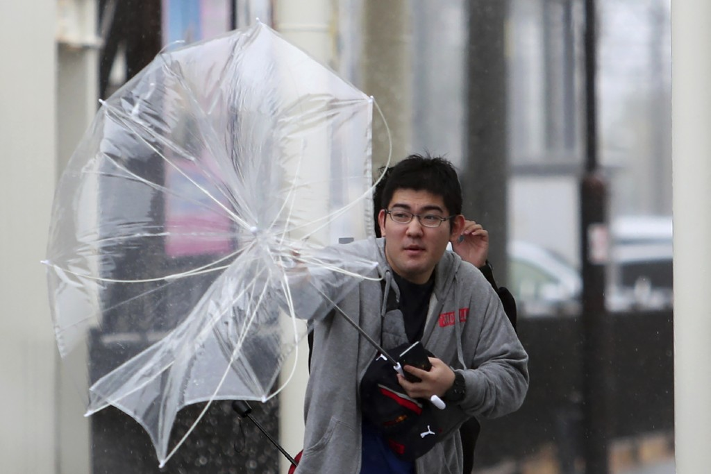 A man struggles with his umbrella against strong wind as Typhoon Hagibis approaches Suzuka, central Japan, Saturday, Oct. 12, 2019. Tokyo and surround
