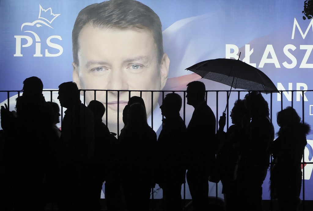 In this photo taken Thursday Sept. 26, 2019 supporters of Poland's ruling right-wing party are standing in line before a candidate's billboard to get
