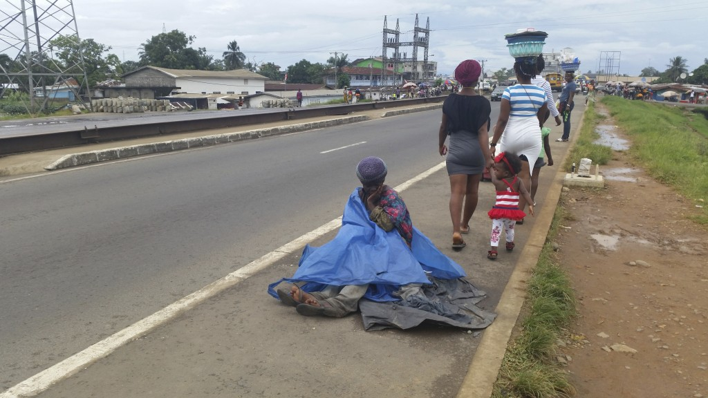 In this Oct. 9, 2019, photo, a mentally ill woman sits on the streets in Monrovia, Liberia. More than a decade after back-to-back civil wars ravaged L