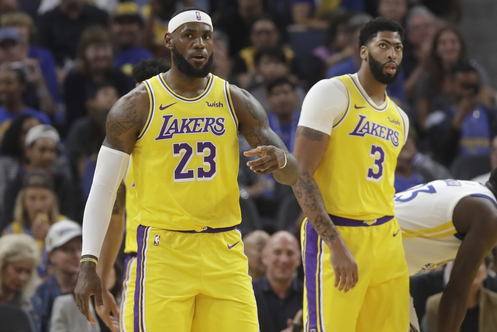 Los Angeles Lakers forward LeBron James (23) reacts in front of forward Anthony Davis (3) during the first half of a preseason NBA basketball game aga...