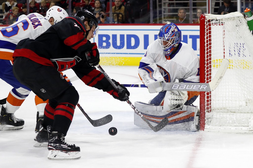 Carolina Hurricanes' Brock McGinn (23) battles with New York Islanders' Ryan Pulock (6) as islanders goaltender Thomas Greiss (1), of Germany, watches