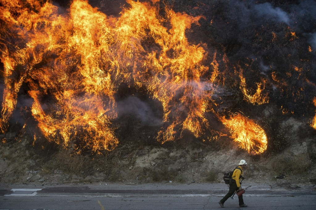 Flames from a backfire, lit by firefighters to stop the Saddleridge Fire from spreading, burn a hillside in Newhall, Calif., on Friday, Oct. 11, 2019....