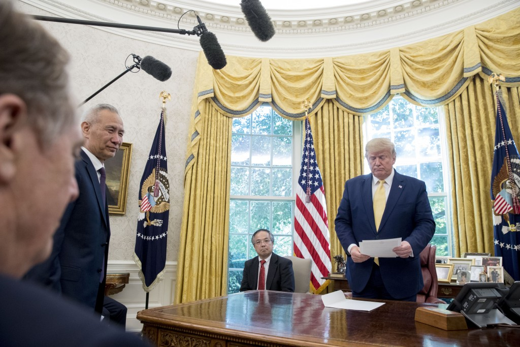 President Donald Trump holds a letter presented to him by Chinese Vice Premier Liu He, second from left, in the Oval Office of the White House in Wash...
