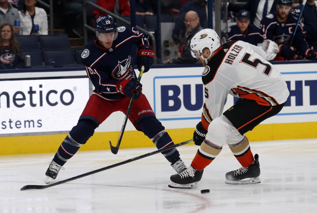 Columbus Blue Jackets forward Riley Nash, left, passes the puck next to Anaheim Ducks defenseman Korbinian Holzer, of Germany, during the second perio