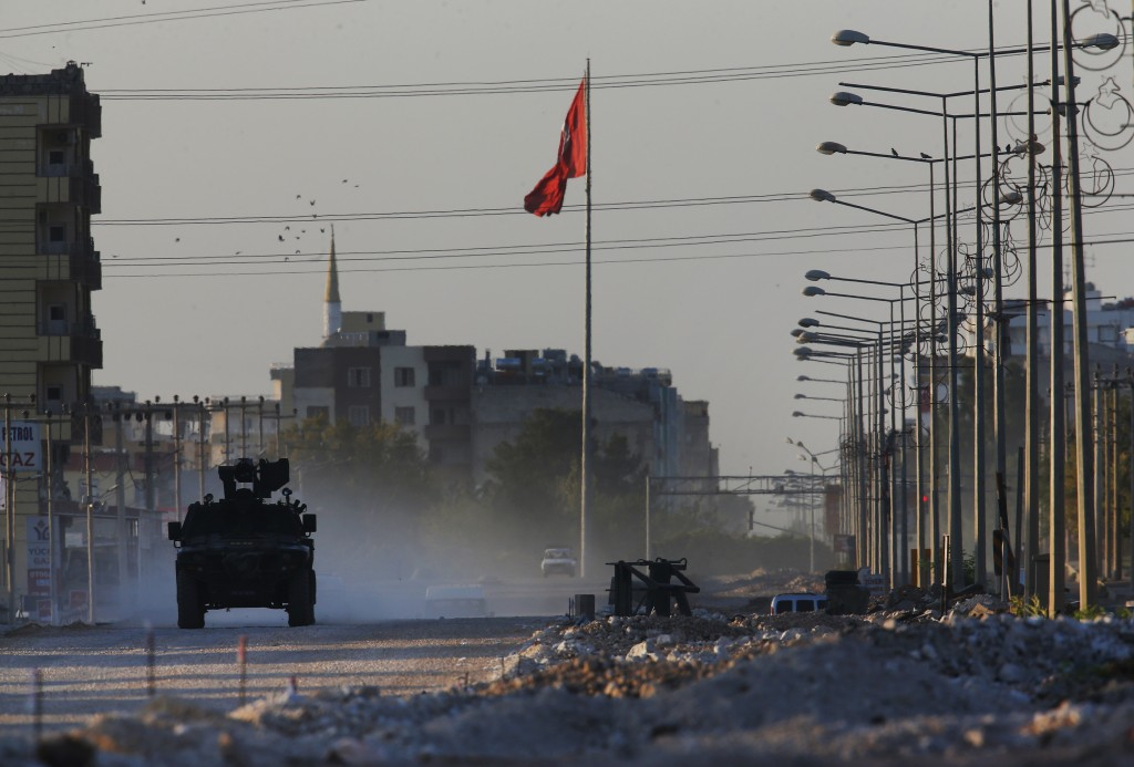 A Turkish police armored vehicle patrols the town of Akcakale, Sanliurfa province, southeastern Turkey, at the border with Syria, Saturday, Oct. 12, 2...