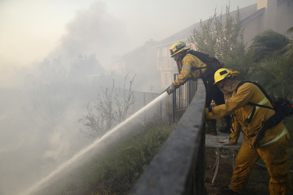 Firefighters make a stand on an advancing wildfire from the backyard of a home Friday, Oct. 11, 2019, in Porter Ranch, Calif. (AP Photo/Marcio Jose Sa