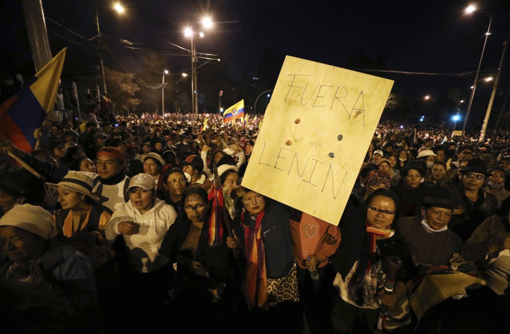 "Indigenous protesters march through Quito, Ecuador, Thursday, Oct. 10, 2019, one with the Spanish message: ""Get out Lenin,"" referring to the president"